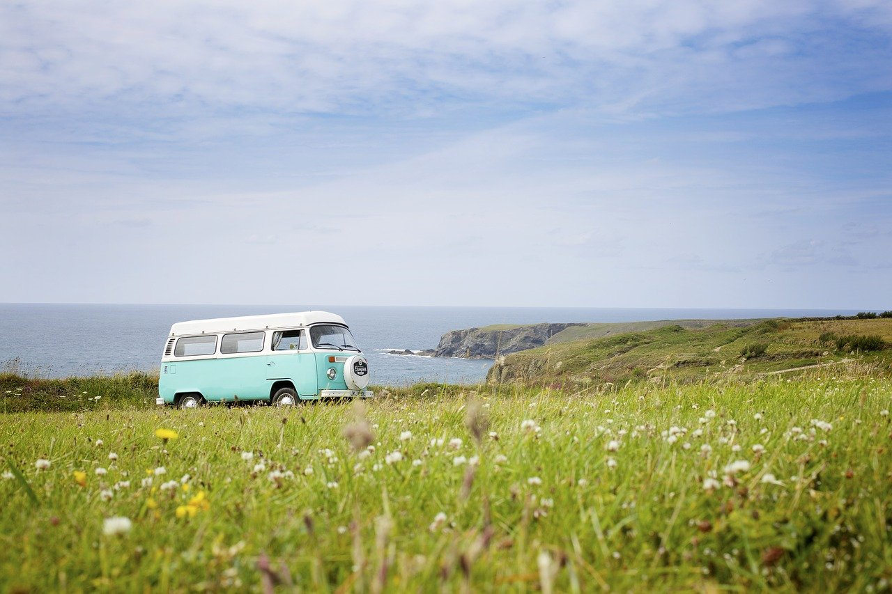 VW camper in field by the sea