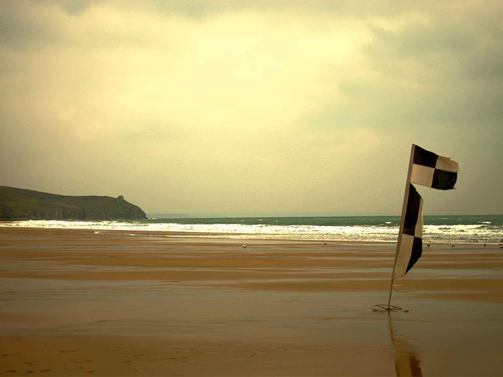 Beach at low tide with flags, Praa Sands, Cornwall
